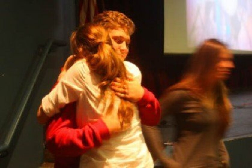 Tommy Solemann gets a hug from a schoolmate during the voluntary meeting of Rachel's Challenge.