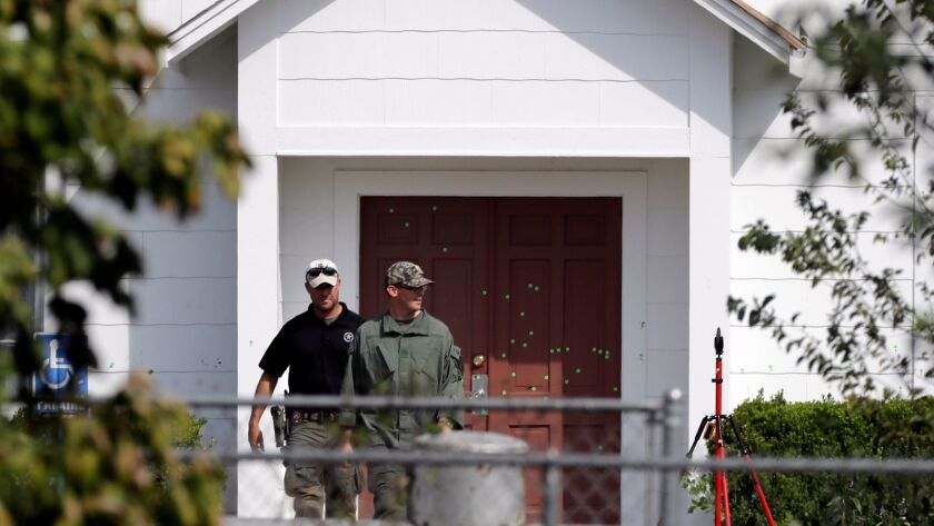 Law enforcement officials walk past the front doors of the First Baptist Church in Sutherland Springs, Texas.