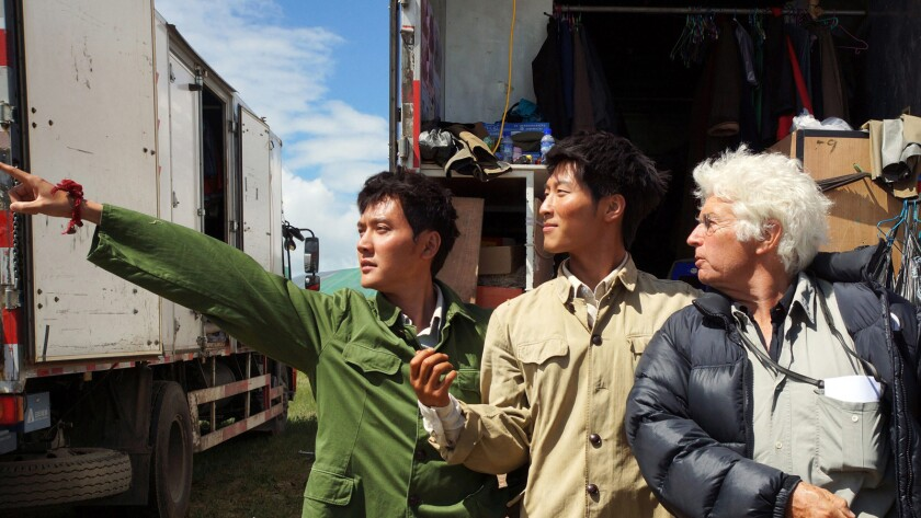 """Chinese actors Feng Shaofeng, left, and Shawn Dou, center, are photographed on set of the film """"Wolf Totem,"""" = with French film director Jean-Jacques Annaud."""