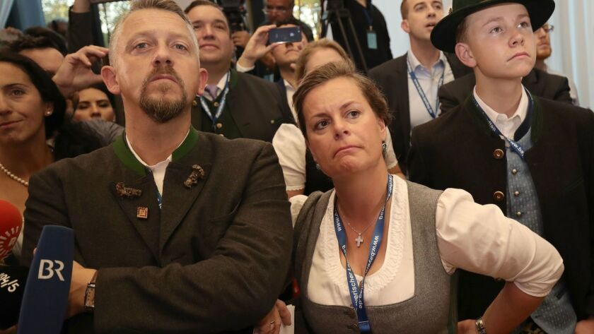 Supporters of the Christian Social Union react after first exit polls were announced on public television at the Bavarian regional government building Sunday.