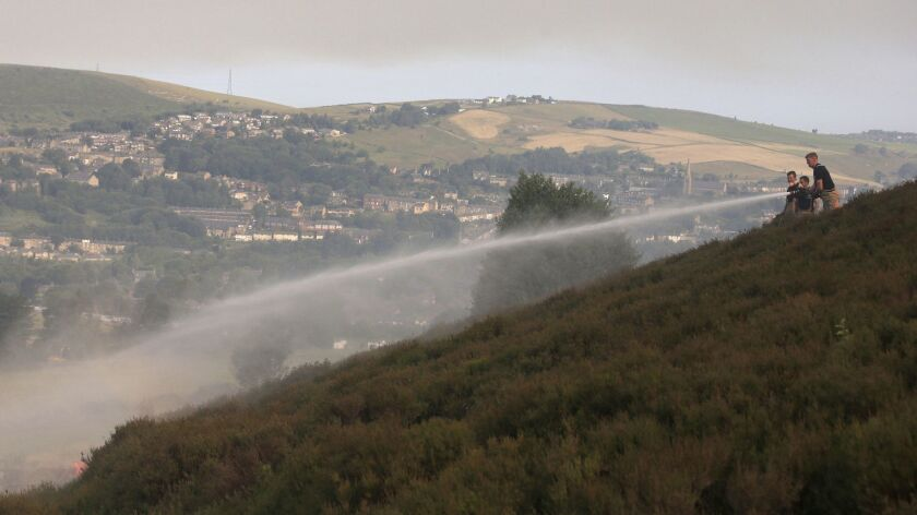 Firefighters work to damp-down land as a wildfire threatens a nearby village, on Saddleworth Moor, E