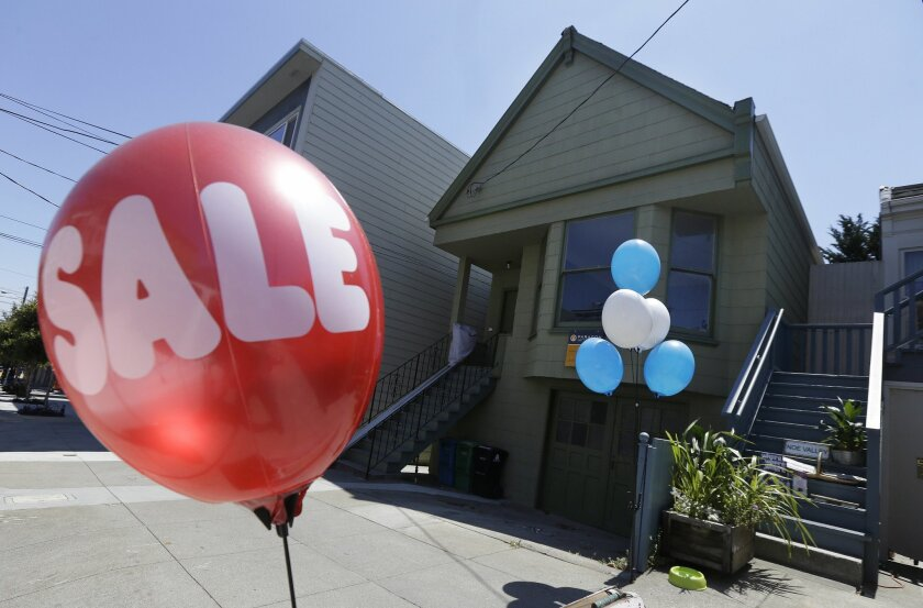 A sale balloon for a nearby store is shown next to a property in the Noe Valley neighborhood just sold for $1.8 million in cash, $600,000 more than its asking price, in San Francisco, Wednesday, July 30, 2014. In the souped-up world of San Francisco real estate, where the median selling price for h