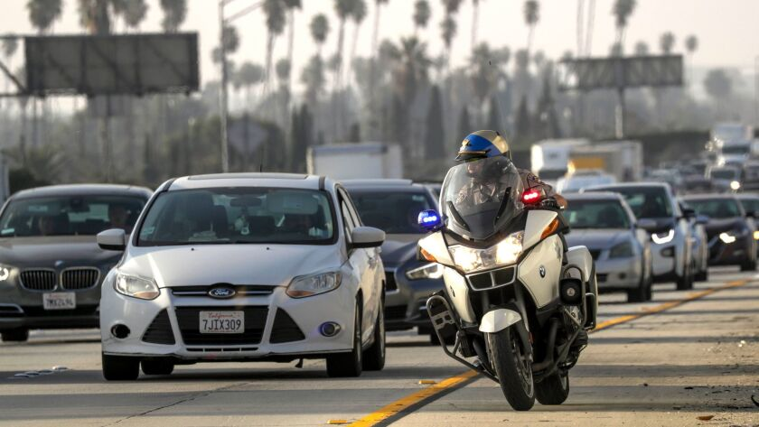 CHP officer L. Montes De Oca goes after a toll evader on southbound toll lanes of 110 Freeway in Los Angeles.