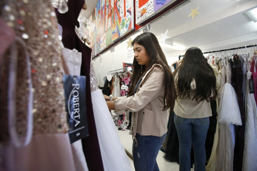 Hayley Elizalde searches for the perfect prom dress at Girls Inc. on Saturday. High school girls received a new prom dress and hair and makeup tips.