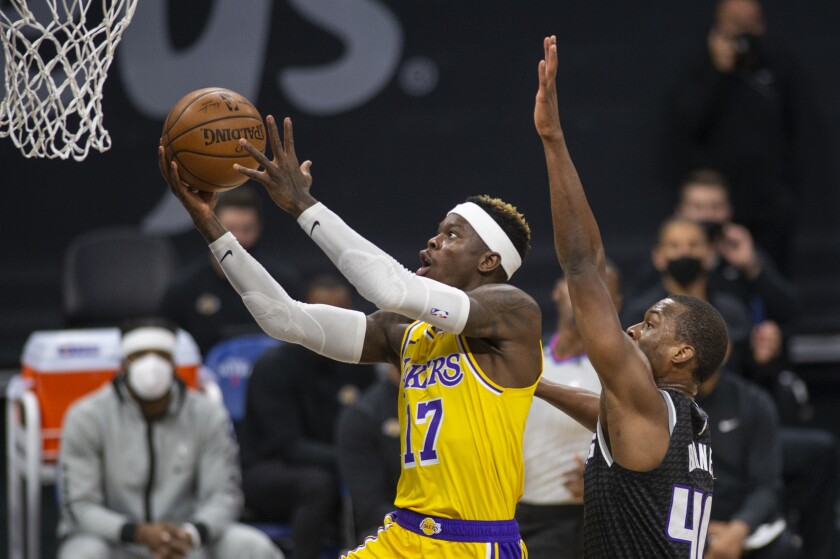 Los Angeles Lakers guard Dennis Schroder (17) scores a basket as he is defended by Sacramento Kings forward Harrison Barnes (40) during the first quarter of an NBA basketball game in Sacramento, Calif., Friday, April 2, 2021. (AP Photo/Hector Amezcua)