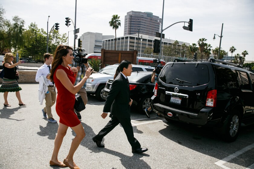 Former Los Angeles County Undersheriff Paul Tanaka, right, walks towards his car as members of the press follow.