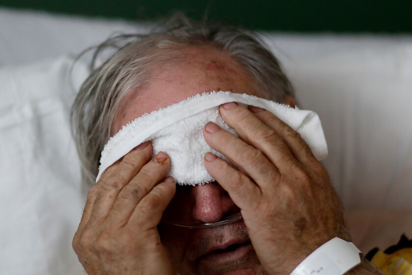FILE - In this Friday, Feb. 9, 2018 file photo, a 73-year-old man places a cold compress on his forehead while battling the flu at a hospital in Georgia. Doctors can test for the flu and get results within a day, but coronavirus testing as of March 2020 is still limited in the United States by availability. (AP Photo/David Goldman)