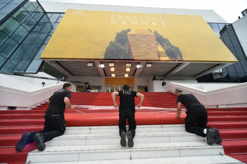 Staff members lay out the red carpet outside the Palais des Festivals in the southeastern French city of Cannes on May 10, the eve of the opening ceremony of the 69th Cannes Film Festival.
