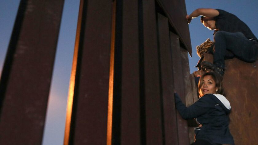 Members of the 'migrant caravan' climb over the U.S.-Mexico border fence on Dec. 3, 2018 in Tijuana, Mexico. Other caravan members used the same place where the border barrier is lower to cross into the U.S. on Tuesday, Dec. 4.