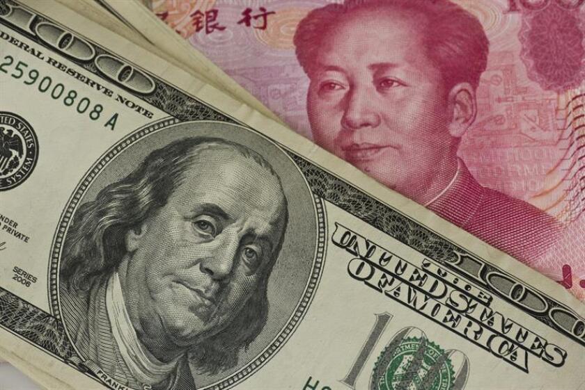 Vista de unos billetes de 100 dólares estadounidenses y renmibis chinos. EFE/Archivo
