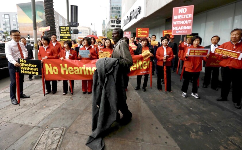 A homeless man stands in front of protesters who are marching against a planned temporary homeless shelter in Koreatown at Wilshire Boulevard and Vermont Avenue.