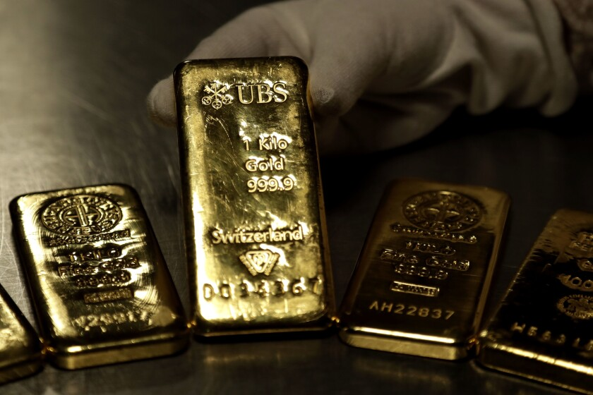 Four gold bars with printing on them gleam.