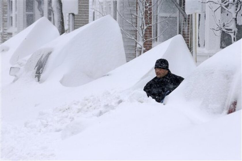 John Silver shovels snow between buried cars in front of his home on Third Street in South Boston, Saturday, Feb. 9, 2013. (AP Photo/Gene J. Puskar)