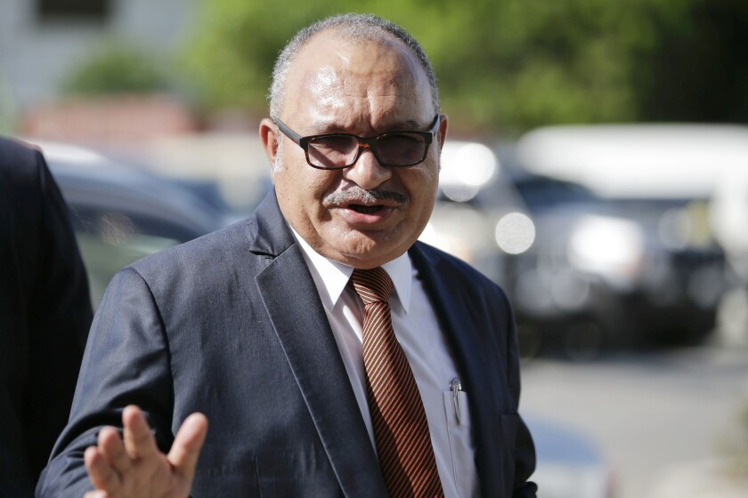 FILE - In this Nov. 14, 2018, file photo, Papua New Guinea Prime Minister Peter O'Neill gestures after inspecting the APEC 2018 International Media Center at Port Moresby, Papua New Guinea. Papua New Guinea police say they have an arrest warrant for former Prime Minister O'Neill for official corruption. The acting police commissioner said O'Neill was in a hotel in the capital but refusing to cooperate. (AP Photo/Aaron Favila, File)