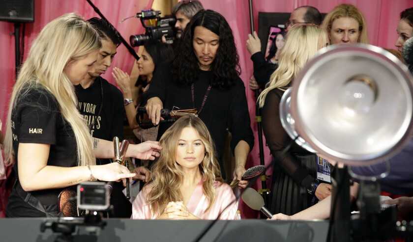 Victoria's Secret model Behati Prinsloo has her hair and makeup done backstage.