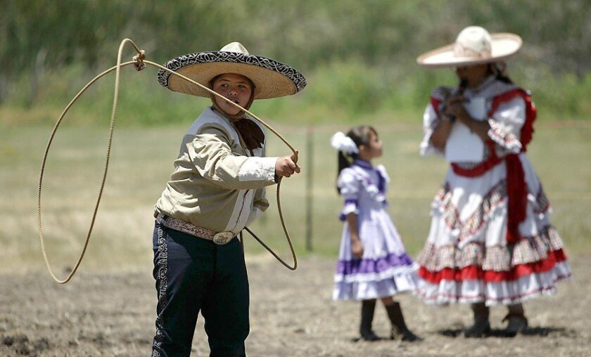Jesus Flores, 12, performs a rope trick while dressed in traditional charro wear during the Fiesta de Guajome in Vista. His mother and sister also took part in the festivities.