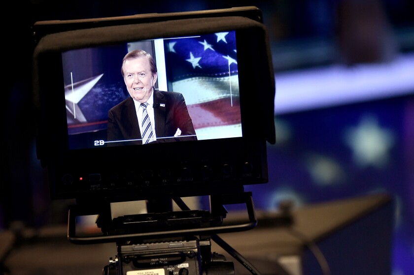 "A monitor on a television camera shows Lou Dobbs hosting ""Lou Dobbs Tonight"" in 2018."