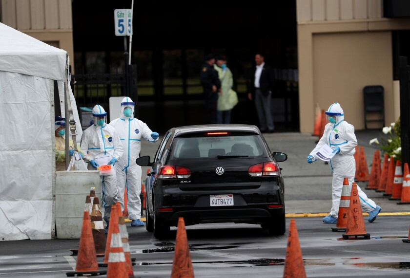 Medical personnel surround a car going through a  drive-through coronaviruscoronavirus test clinic March 16 at the  San Mateo County Event Center.