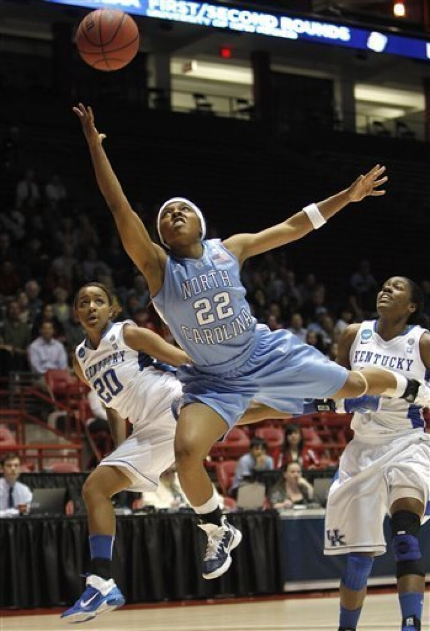 North Carolina's Cetera DeGraffenreid (22) gets fouled by Kentucky's Maegan Conwright (20) as she goes up for a shot while Kentucky's Victoria Dunlap (34) looks on during the first half of a second-round NCAA women's college basketball game, Monday, March 21, 2011, in Albuquerque, N.M. (AP Photo/Ross D. Franklin)
