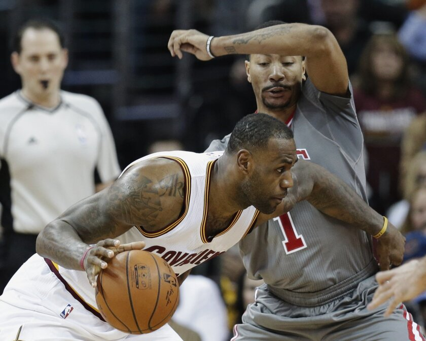 Cleveland Cavaliers' LeBron James (23) drives past Chicago Bulls' Derrick Rose (1) in the first half of an NBA basketball game Saturday, Jan. 23, 2016, in Cleveland. (AP Photo/Tony Dejak)