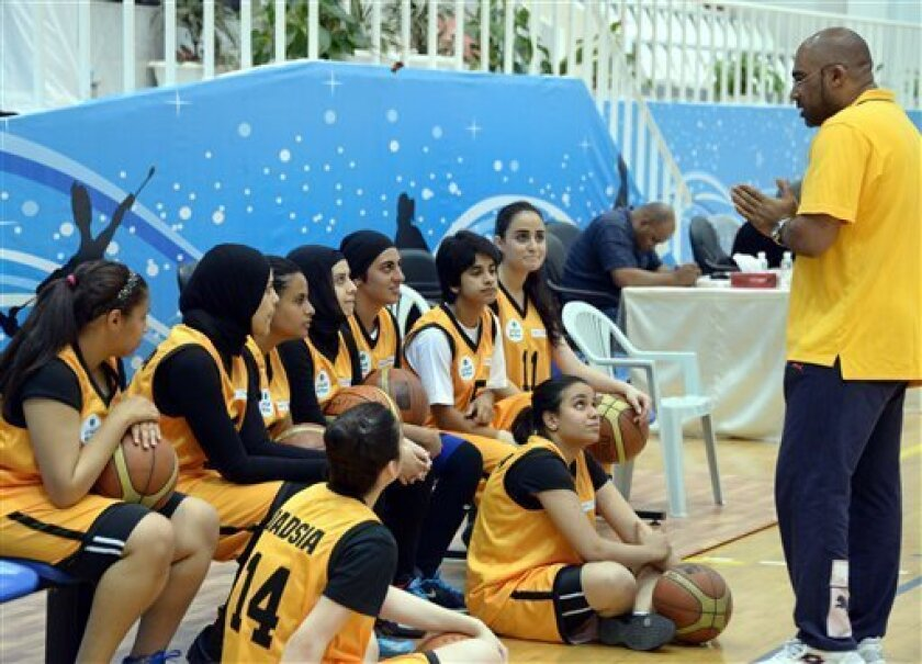 Kuwait's Qadsiya Club women basketball team listen to their coach, during the Women's Games, at Salwa Al Sabah Sports Center in Qurein, Kuwait, Thursday, May 9, 2013. The event is part of a new initiative launching sports leagues for women, including basketball, table tennis and athletic leagues fo