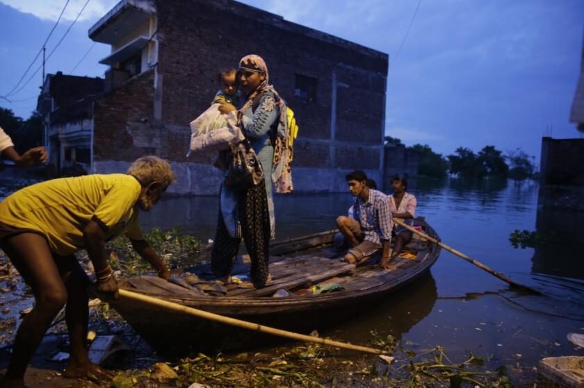 Un grupo de personas se pone a salvo durante una inundación provocada por una crecida del río Ganges en Allahabad, India. (AP Foto/Rajesh Kumar Singh)