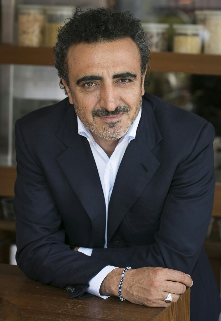 This April 30, 2015 photo provided by Chobani LLC shows company founder and CEO Hamdi Ulukaya at the Chobani Soho cafe in New York. Ulukaya says he will join some of the world's richest individuals in pledging to give away at least half his wealth, which has been estimated at $1.41 billion. (Mark Von Holden/AP Images for Chobani, LLC)