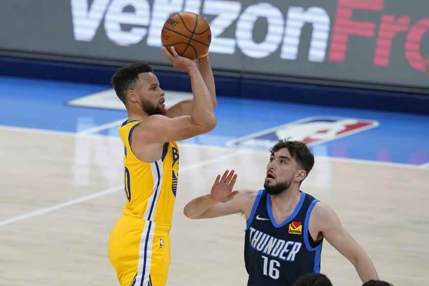 Stephen Curry, de los Warriors de Golden State, dispara frente a Ty Jerome, del Thunder de Oklahoma City, en el encuentro del miércoles 14 de abril de 2021 (AP Foto/Sue Ogrocki)