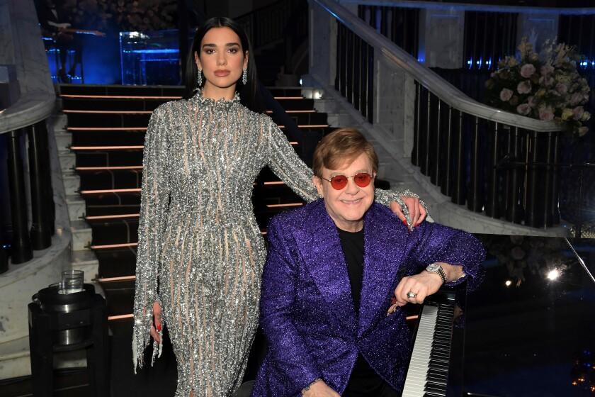 Dua Lipa and Elton John pose together beside a piano