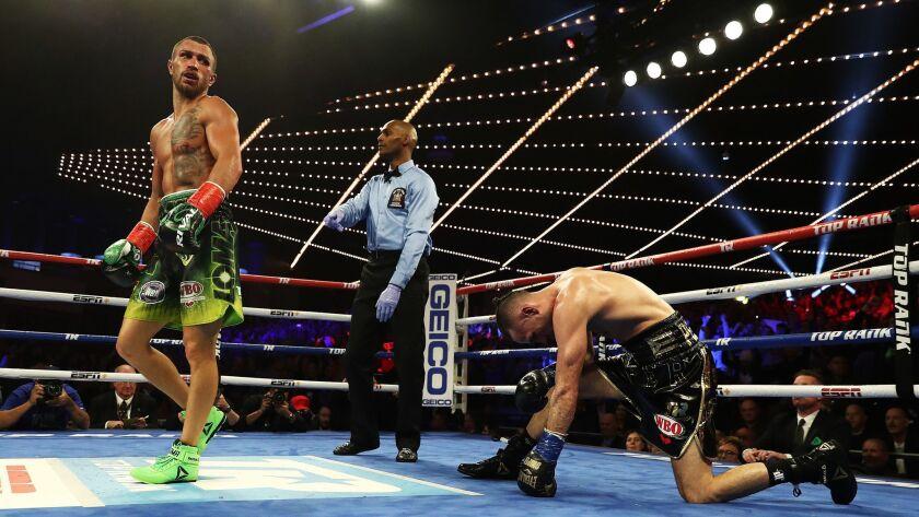 Vasiliy Lomachenko knocks down Jose Pedraza in the eleventh round during their WBA/WBO lightweight unification bout.