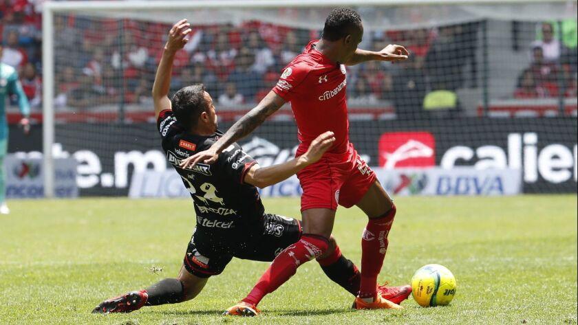 Tijuana's Omar Mendoza (left) maneuvers for control of the ball against Toluca's Luis Quinones during Tijuana s 4-1 loss in the Liga MX semis last spring.