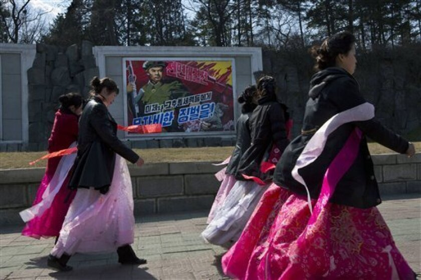 """North Korean women pass by roadside propaganda depicting a North Korean soldier killing a U.S. soldier in Pyongyang, North Korea on Wednesday, April 10, 2013. The poster reads in Korean """"Life or Death Battle. Merciless Punishment to U.S. Imperialists and Puppet Traitors."""" (AP Photo/David Guttenfelder)"""