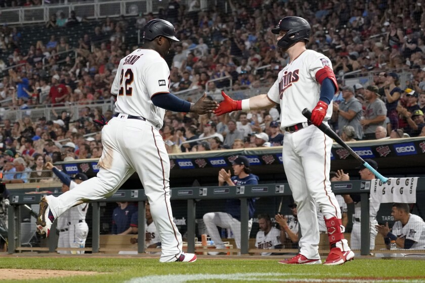 Minnesota Twins' Ryan Jeffers, right, congratulates Miguel Sano after Sano scored on a hit by Nick Gordon off Los Angeles Angels relief pitcher Steve Cishek during the sixth inning of a baseball game Friday, July 23, 2021, in Minneapolis. The Twins won 5-4. (AP Photo/Jim Mone)