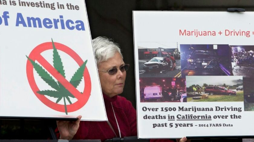 In this Tuesday, Oct. 4, 2016 file photo, Illona Mager holds a pair of signs during a rally against Proposition 64 at the Capitol in Sacramento, Calif.