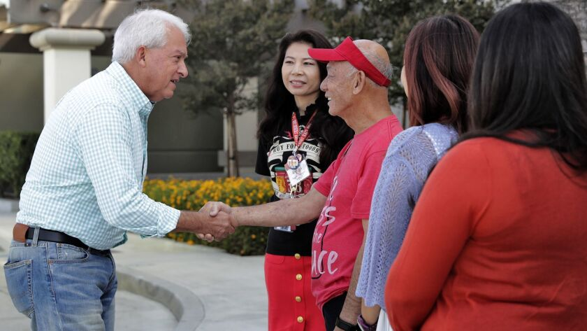 Republican gubernatorial candidate John Cox, left, greets David Tran, owner of Huy Fong Foods in Irwindale, and employees Wednesday as he kicks off his campaign bus tour.