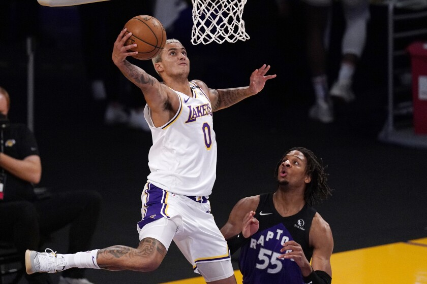 Lakers forward Kyle Kuzma drives past Raptors forward Freddie Gillespie for a reverse dunk.