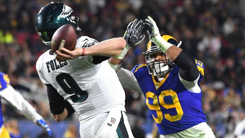 Eagles quarterback Nick Foles gets a pass off despite pressure from Rams defensive tackle Aaron Donald during the second quarter Sunday.