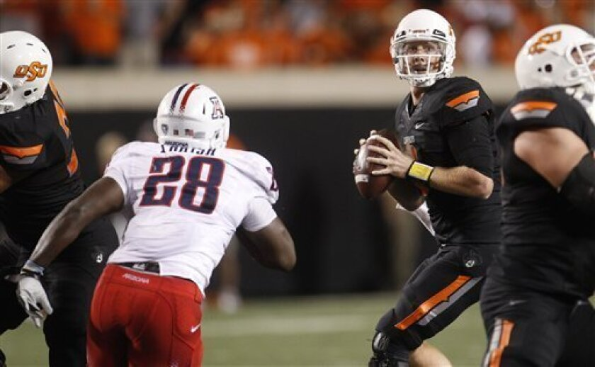 Oklahoma State quarterback Brandon Weeden, right, looks for a receiver as Arizona defensive end C.J. Parish, left, moves in to defend in the second quarter of an NCAA college football game in Stillwater, Okla., Thursday, Sept. 8, 2011. (AP Photo/Sue Ogrocki)