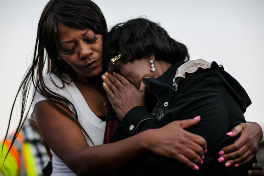 Catherine Mazzucco, right, mother of Marcus McClendon, 52, breaks down during a vigil at the spot where McClendon was shot.