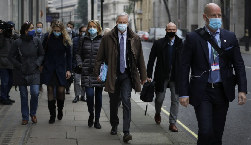 EU Chief Negotiator Michel Barnier, centre, with his team as he walks to a conference centre in Westminster in London, Sunday, Nov. 29, 2020. Teams from Britain and the European Union are continuing face-to-face talks on a post-Brexit trade deal in the little remaining time. (AP Photo/Kirsty Wigglesworth)