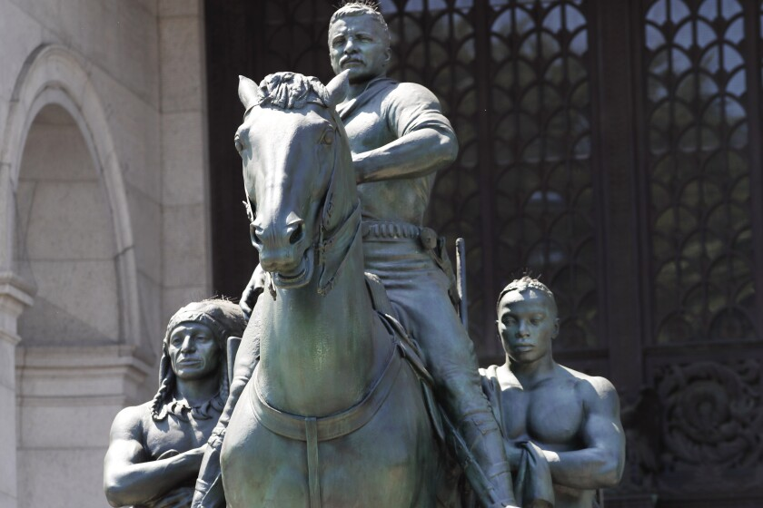 FILE — In this June 22, 2020 file photo, a statue of Theodore Roosevelt on horseback guided by a Native American man, left, and an African man, right, sits in front of the American Museum of Natural History, in New York. The New York City Public Design Commission voted unanimously Monday, June 21, 2021, to relocate the statue to a yet-to-be-designated cultural institution dedicated to Roosevelt's life and legacy. (AP Photo/Kathy Willens, File)