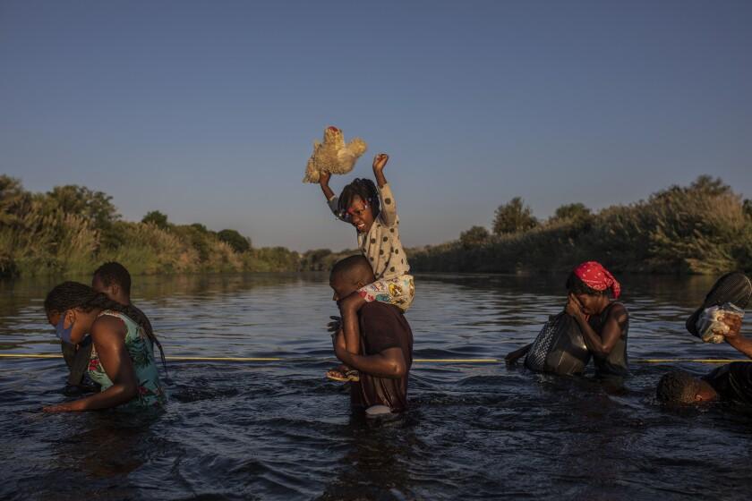 Migrants wade across the Rio Grande from Del Rio, Texas, to return to Ciudad Acuña, Mexico.