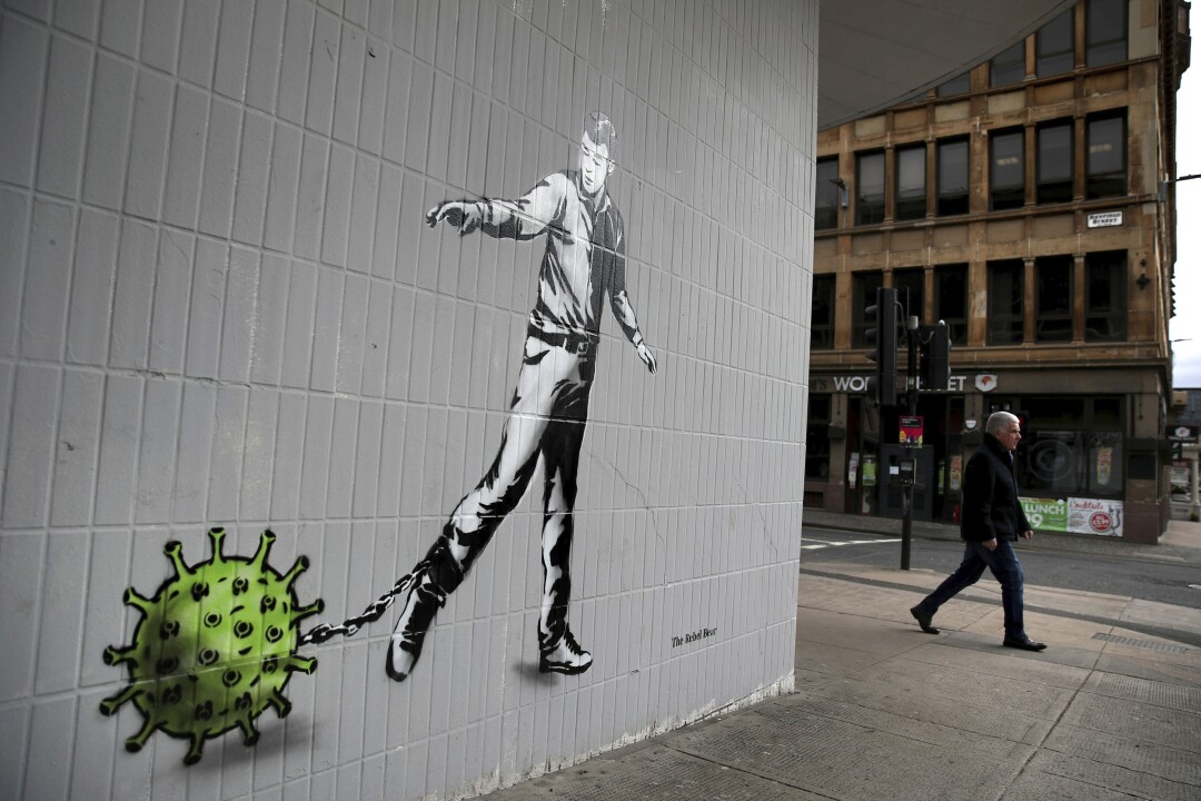 SCOTLAND: A person walks past a piece of coronavirus-themed art by the artist known as the Rebel Bear after it appeared on a wall on Bath Street in Glasgow, Scotland.
