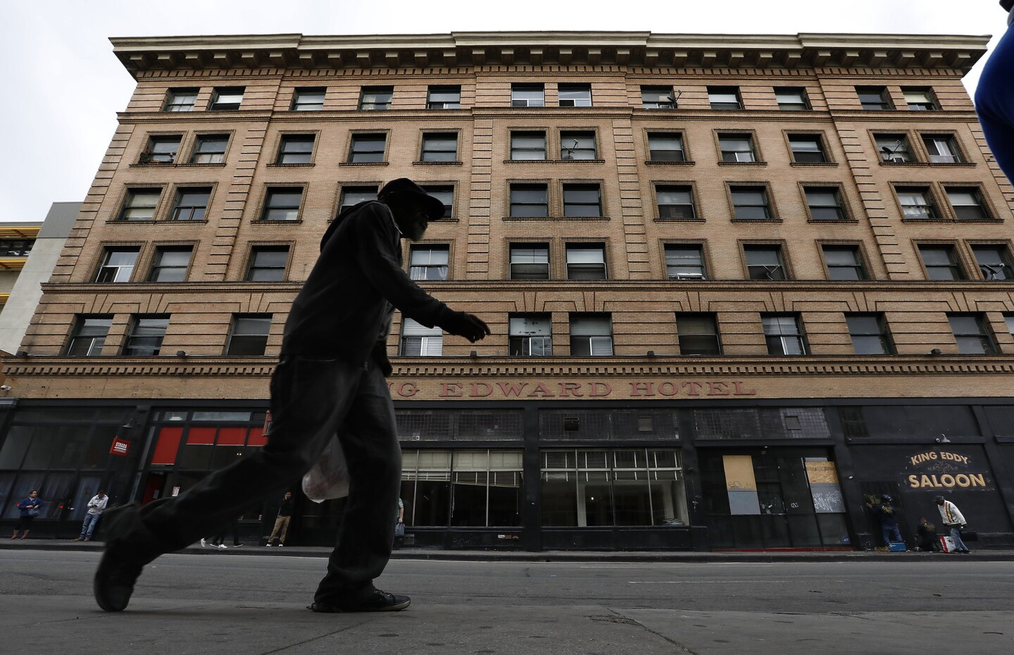 A pedestrian walks along 5th St. in downtown Los Angeles with the King Edward Hotel seen in the background. The Aids Healthcare Foundation has purchased the 106 year old hotel and plans to lease its 150 rooms to homeless people.