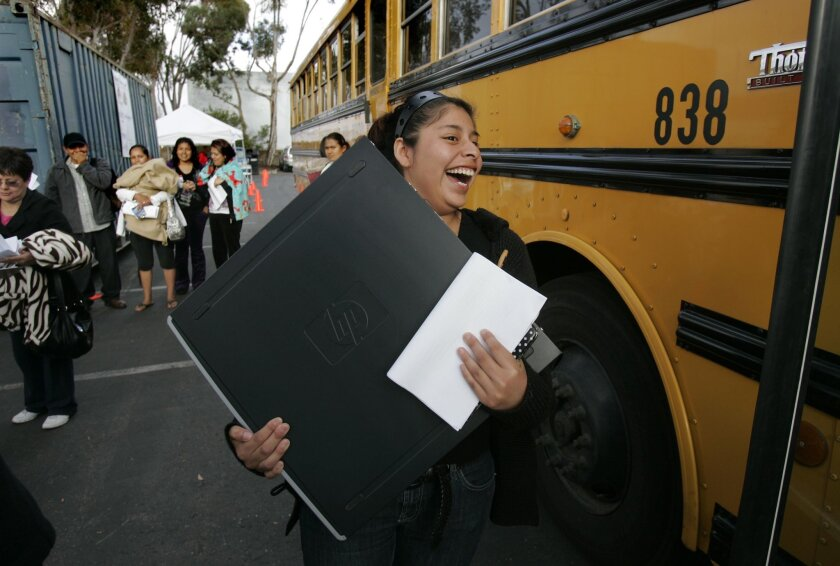 Fallbrook High student Jessica Cruz, 18, carries the computer she just received for free as part of the Computers 4SD Kids distribution Wednesday on Miramar Road.