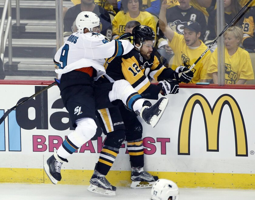 San Jose Sharks' Dainius Zubrus (9) crashes into Pittsburgh Penguins' Ben Lovejoy (12) during first period in Game 1 of the Stanley Cup final series Monday, May 30, 2016, in Pittsburgh. (AP Photo/Gene J. Puskar)