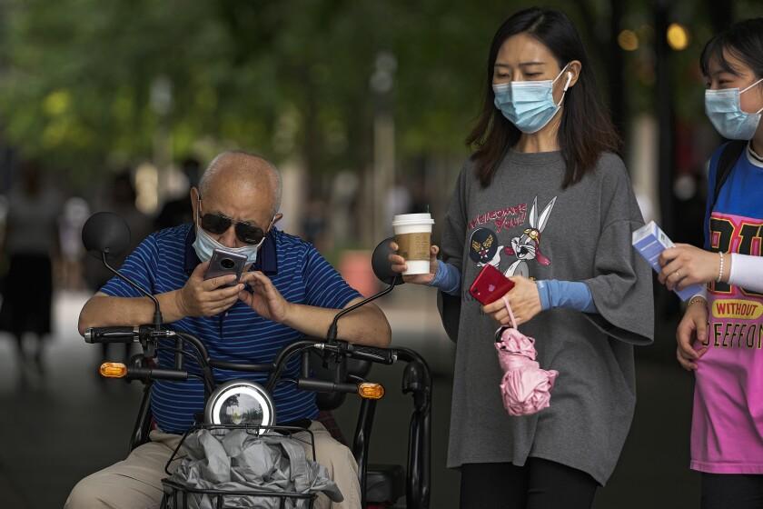 Dos mujeres con mascarillas junto a un hombre que revisa su celular, en Beijing