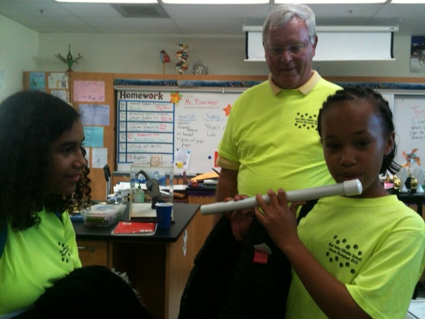 Ariyia Minter (right), 13, plays the flute she made from PVC pipe as classmate Sariah Mevs, 14, who made a slap tube instrument for the Science Olympiad, watched during a celebration last month. Behind them is Bear Valley Middle School science teacher Randy Will.