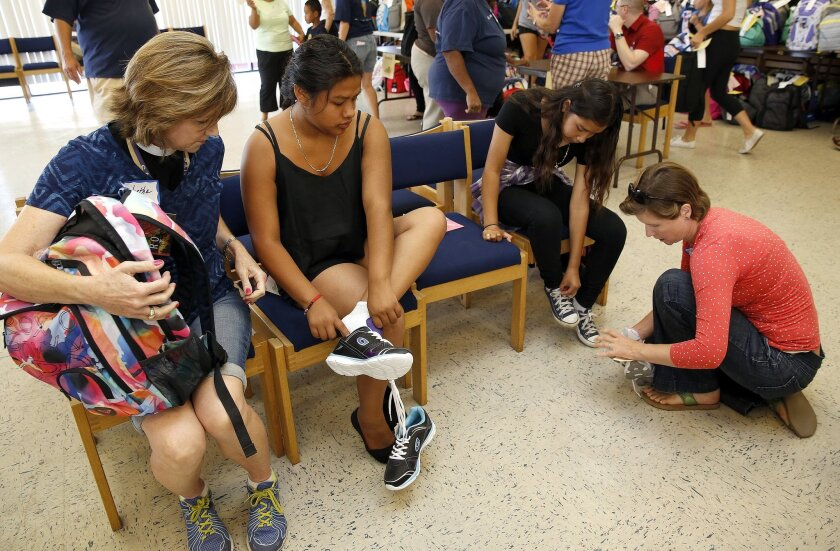 The Rev. Martha Anderson (left), of St. Peter's Episcopal Church in Del Mar helped Brigitte Mayo, 16, try on new sneakers during the St. Mark's Catholic Church's 4th Annual Back 2 School Bash on Saturday, On the right is Brigitte's sister, Diana Mayo, 13,trying on sneakers with the help of volunteer Helen Davies.