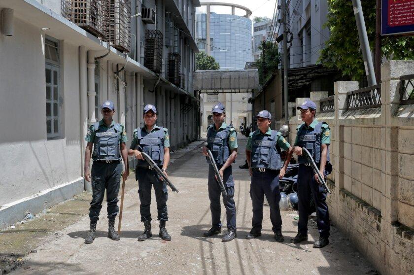 Policías de Bangladesh custodian el 27 de julio del 2016 la morque donde yacen los cadáveres de nueve insurgentes islámicos muertos en una operación policial en Dhaka, Bangladesh. El padre de uno de ellos no puede creer que su hijo haya dejado la vida que llevaba y se haya sumado a los insurgentes. (AP Photo, File)